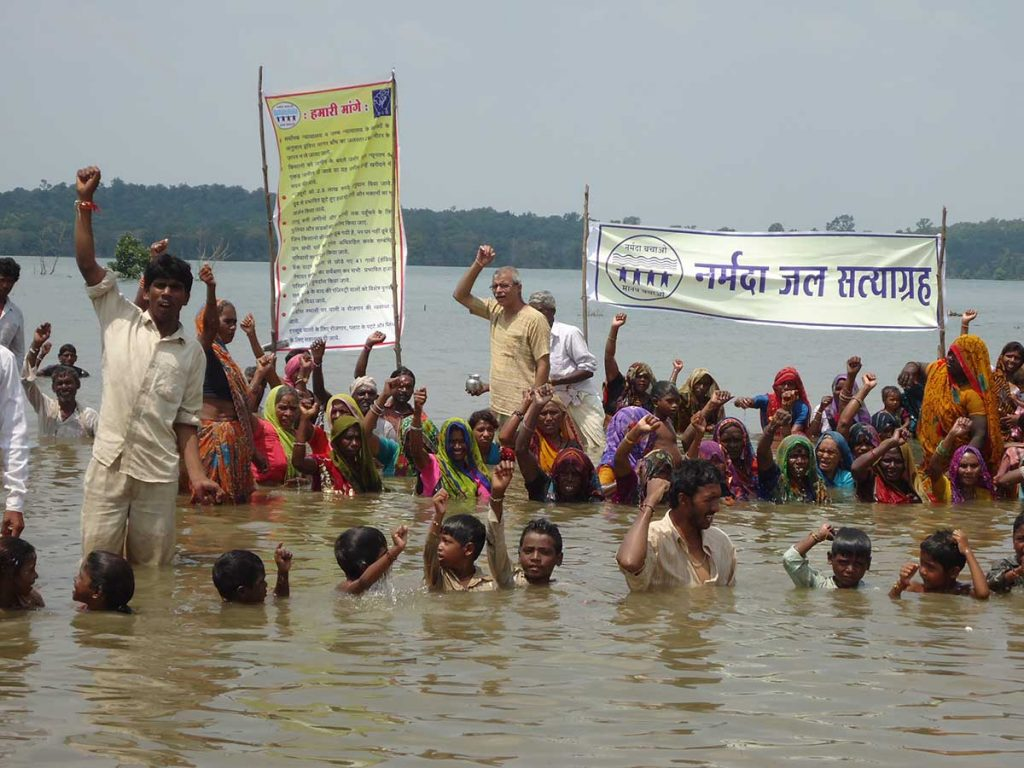 Protestors stand in rising waters to demand full rehabilitation of affected communities
