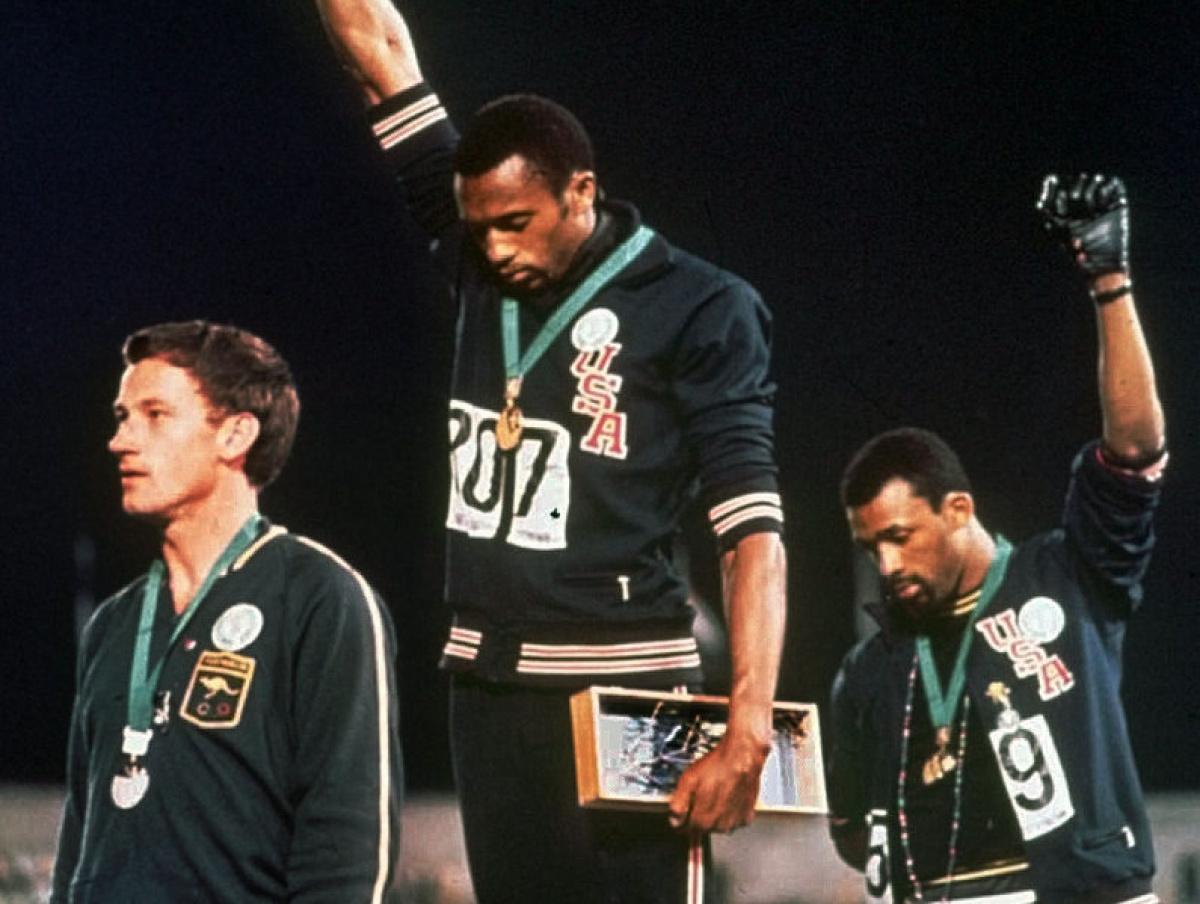 Con los puños enguantados extendidos hacia el cielo, los atletas estadounidenses Tommie Smith y John Carlos miran hacia abajo cuando suena el himno nacional de los Estados Unidos en los Juegos Olímpicos de México el 16 de octubre de 1968 (AP Photo).