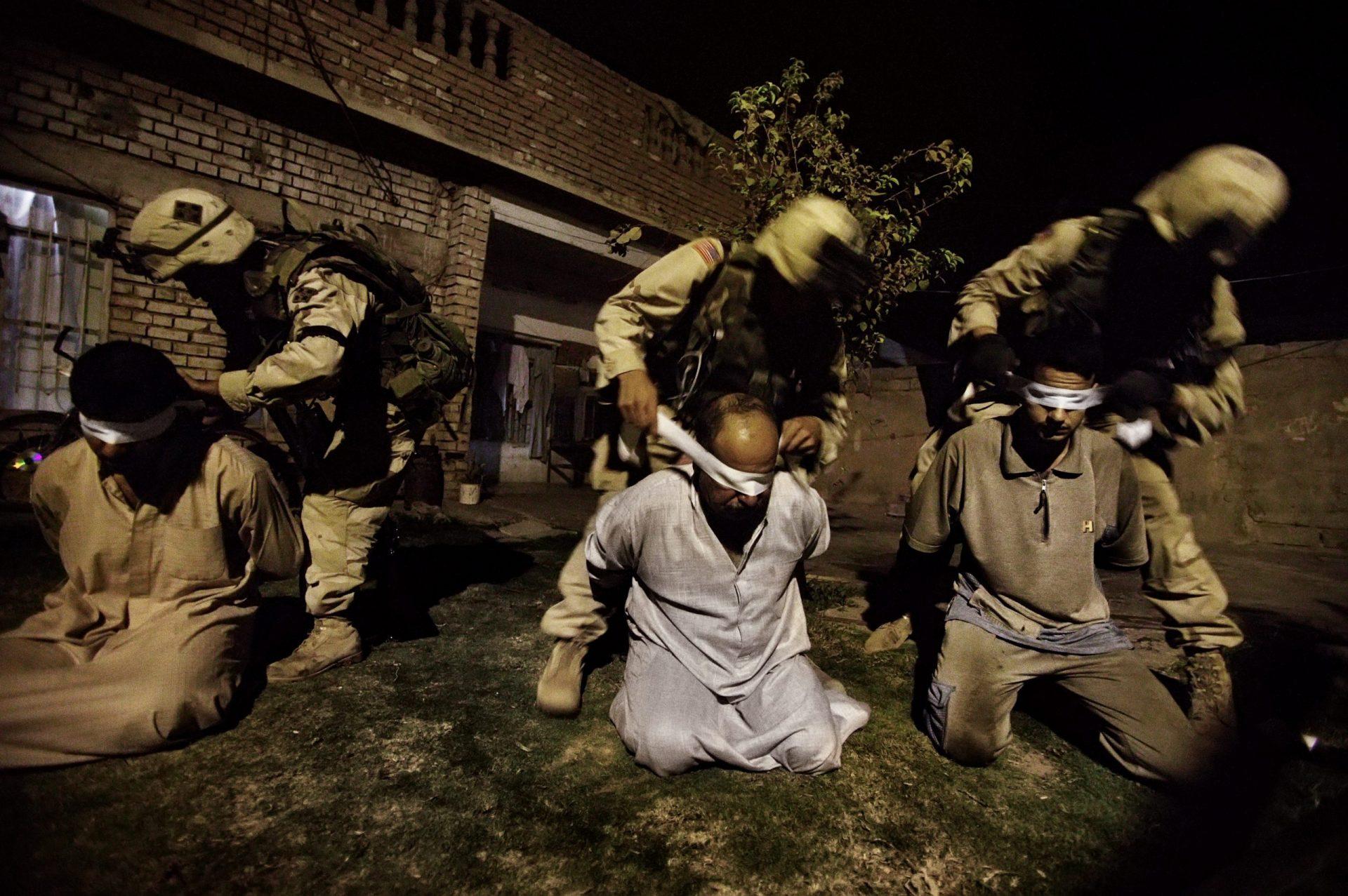Pie de foto: TIKRIT, Irak, 24 de septiembre de 2003: Los soldados estadounidenses del 1er Batallón (22º regimiento de infantería, compañía C) de la Cuarta División del Ejército de los Estados Unidos vendan los ojos a hombres sospechosos de ser traficantes de armas y explosivos en Tikrit.